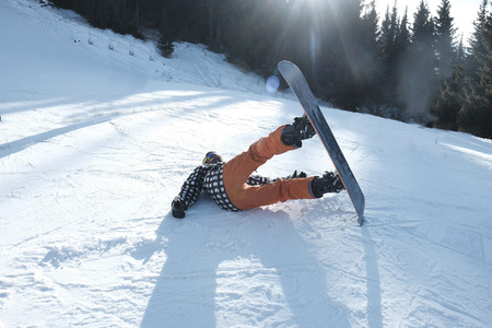 snowboarder with a board tumbles in the snow