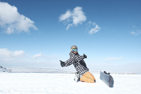 joyful snowboarder sits in the snow and arms outstretched, near the snowboard board