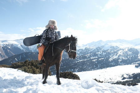 male traveler riding a horse in the snowy mountains. Fur cap on his head 스톡 콘텐츠