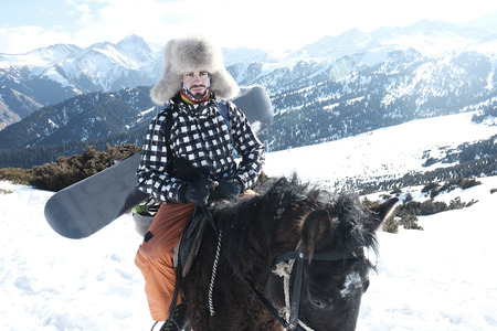 male traveler rides a horse in the snowy mountains. On the head is a fur hat. behind a snowboard board.