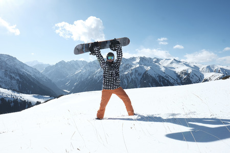 snowboarder raises a snowboard over his head, stands on the snow clear day