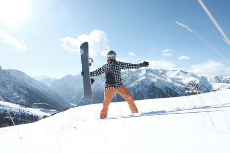 snowboarder holding a snowboard in his hands, standing in the snow, a clear day. snow mountains, 스톡 콘텐츠