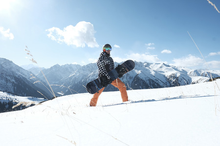 snowboarder holding a snowboard in his hands, standing in the snow, a clear day. 스톡 콘텐츠