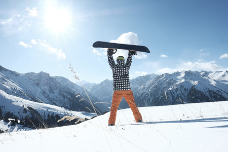 snowboarder raises a snowboard over his head, stands on the snow clear day, Imagens