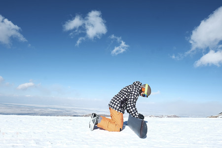 snowboarder sitting in the snow hugging a snowboard board,
