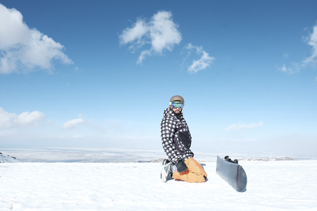 a snowboarder is sitting in the snow, a snowboard board is near,