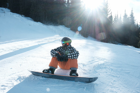 snowboarder with a fastened board sits on the snow, 스톡 콘텐츠