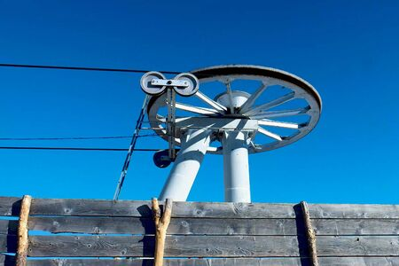 Rotating wheels of skiing drag lift on top of mountains slope, small ski resort 스톡 콘텐츠 - 138448690