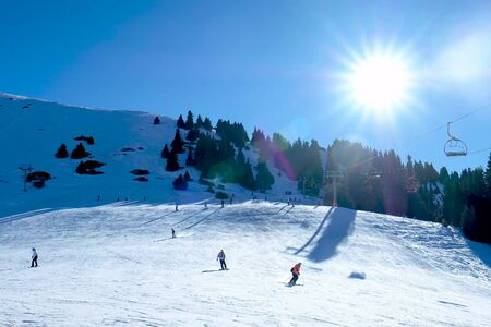 skiers and snowboarders descend from the mountains. Working lift. Blue sky, the sun is shining