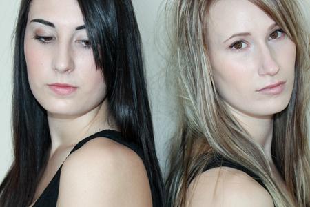 Two beautiful women standing back to back photo