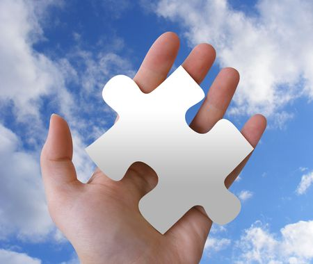 A hand is holding a puzzle piece against a cloudy sky. photo