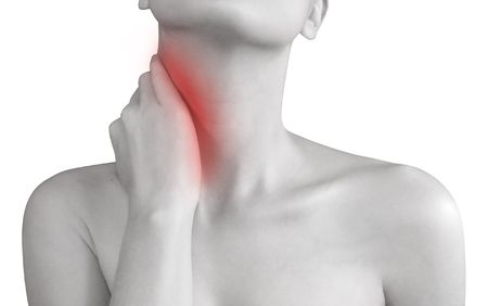 A woman is holding her hand to her neck and there is a red spot on the neck where the pain is. Stock Photo