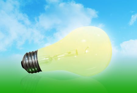 A yellow light bulb is in front of a nature background with a blue sky filled with clouds and a green base. Stock Photo - 4771620