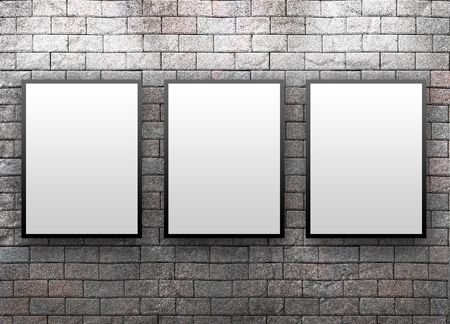 them: Three blank, white canvas frames are hanging on a brick wall. Light is shining down on them.