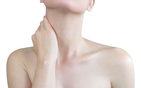 A woman is holding her hand to her neck. photo