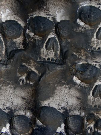 grotesque: Several skulls are on a wall. Use this for a background.