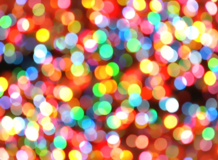 Bright, colorful, rainbow lights are blurred and shiny. Makes a good Christmas celebration or Nightclub background for festivals.