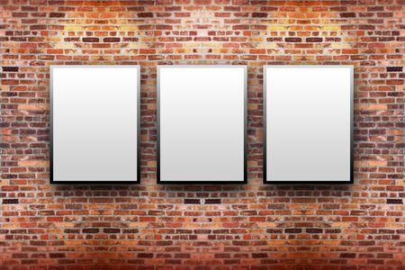 3 개의 빈 흰색 캔버스 프레임 벽돌 벽에 걸려있다. 빛이 그들 위에 비치고 있습니다.