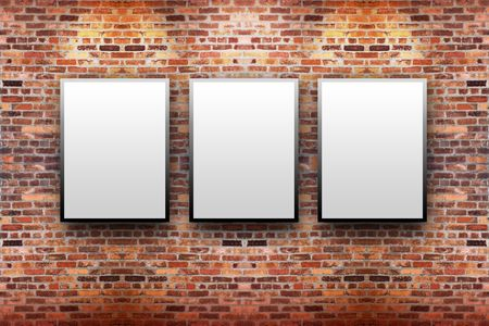 gallery wall: Three blank, white canvas frames are hanging on a brick wall. Light is shining down on them.