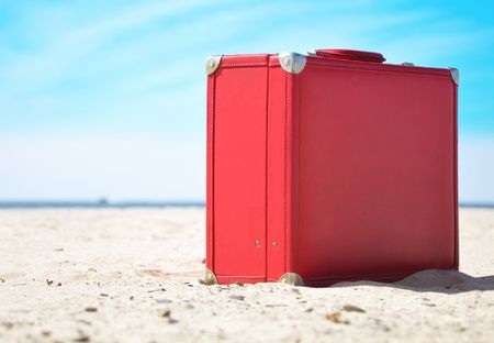 A red travel suitcase is alone on a beach with the lake or ocean in the background. Use this image to represent a voyage, getaway to a  tropical beach vacation in the sun.