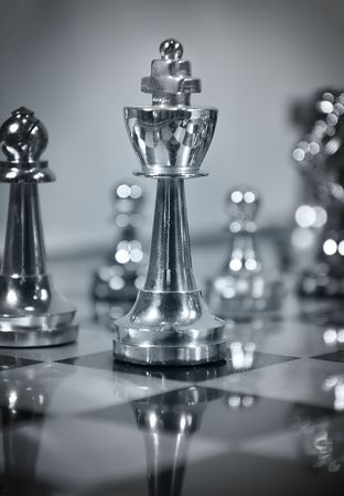 A closeup of a chess game with a king piece. Color scheme is blue. Use it to represent business strategy, competition or playing a simple game of chess.