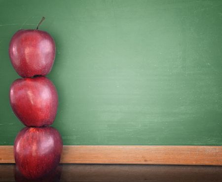 Three red apples are stacked up and leaning against a green school chalkboard. Use the photo for a classroom, school or education concept.