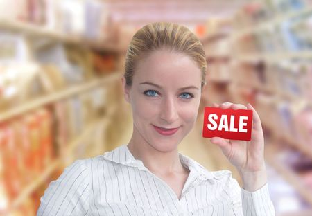 A woman is holding up a red card that has the word SALE on it. She looks happy and is standing in a department store. photo