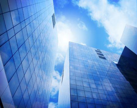 Edificios de negocios de la ciudad azul brillante están subiendo al cielo donde hay nubes y sol. Los rascacielos pueden ser un lugar de trabajo o una Oficina.  Foto de archivo