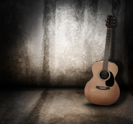 An wooden acoustic guitar is against a grunge textured wall  The room is dark with a spotlight for your copyspace  Use it for a music or concert concept