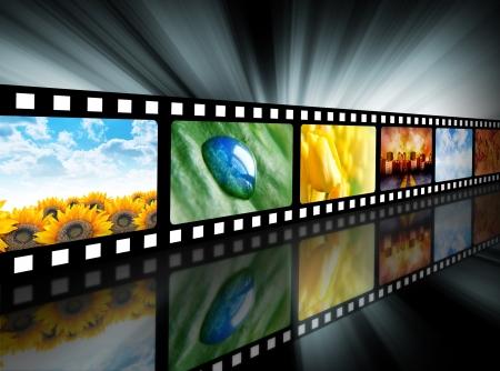Een film reel heeft verschillende natuur foto's op en is er een gloeiende zwarte achtergrond. Gebruik het voor een media-technologie concept. Stockfoto