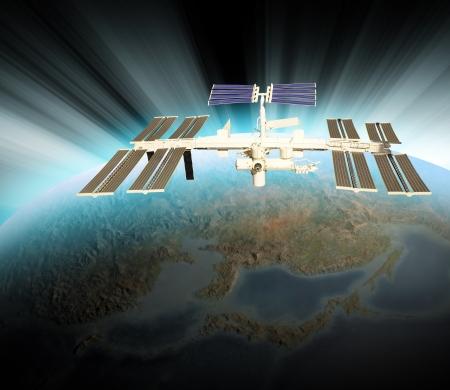 satelite: Un sat�lite est� por encima de la Tierra y est� en �rbita alrededor del planeta. Hay un resplandor blanco azul del sol en el horizonte. Util�zalo para un espacio o tema de la tecnolog�a. Foto de archivo