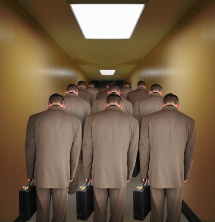 strive: Business men are walking down a hallway to do office work. The heads are down to symbolize pressure or powerlessness from the job. Use it for an unemployment or a career concept.
