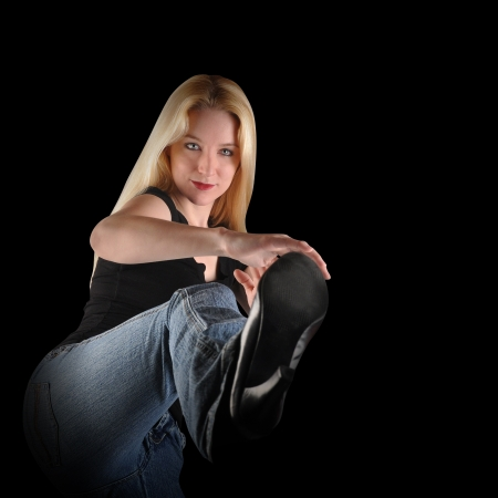 A young woman is kicking up and looks tough and serious on a isolated black background  Add your message to the blank area  Use it for a strength or confidence concept  photo