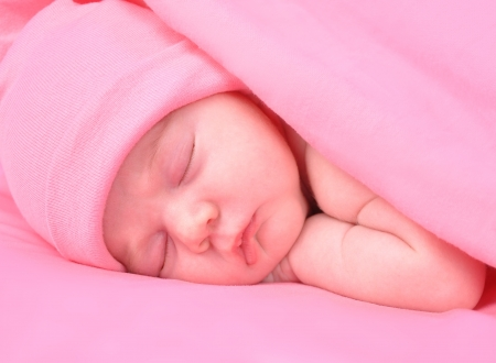 A newborn baby girl is sleeping on a pink background with a blanket  She is wearing a hat  Use it for a childhood, parenting  or innocence theme  photo