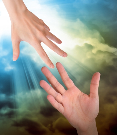 forgiveness: A hand is reaching out or grabbing for help from another hand in the sky