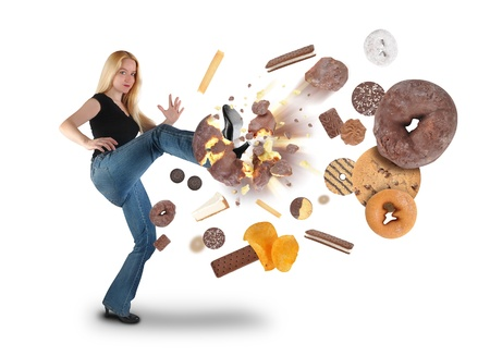 A young woman is kicking a donut on a white background within an assortment of junk food  There are cookies, chips and ice cream  Use it for a diet or nutrition concept   Imagens