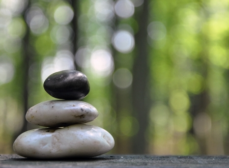 peace of mind: A stack of three zen rocks are in the forest with trees in the background to add a text message  Stock Photo