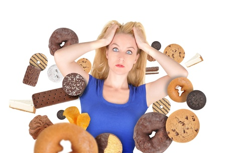 diabetes: A woman has sweet food snacks around her on a white background  She has fear and there are donuts and cookies  Use it for a health or diet concept