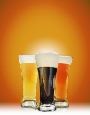 bier glazen: Drie koud bier glazen hebben schuim en zijn op een gouden achtergrond