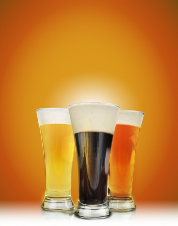 beer pint: Three cold beer glasses have foam and are on a golden background Stock Photo