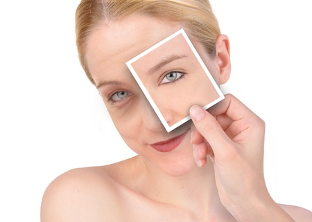 A hand is holding up a photo of a young, eye on a wrinkled woman s face  She is isolated on a white background