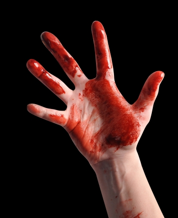 A bloody red hand is isolated on a black background and reaching up