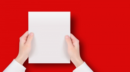magazine page: Hands are holding a blank white piece of paper on a red background  Add your text message easily   Stock Photo