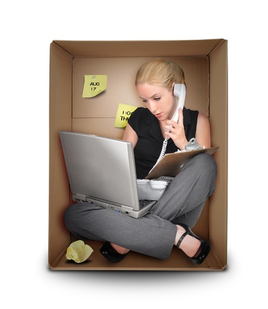 confined: A young business woman is working on a laptop and talking on a phone in a box representing a small office  Use it for a job occupation or entrepreneur concept