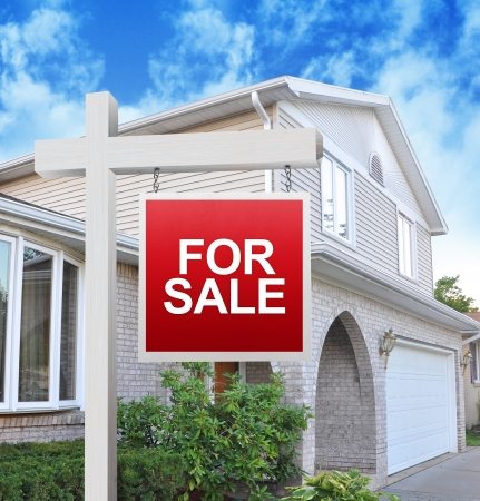 A home is advertising a for sale sign on a wooden sign post in red. Use it for a housing market concept.  photo