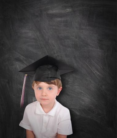 Een jonge jongen draagt een graduation cap en kwast tegen een zwarte krijtbord Voeg uw tekst aan de copyspace Gebruik het voor een opleiding of school concept