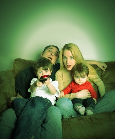 they are watching: A family is watching television together on a couch and look shocked at what they see.