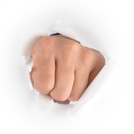A fist hand is punching through a white piece of paper  Use it for an anger or impact concept