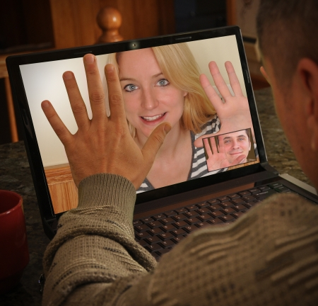 talk to the hand: A girl and boy are communicating on a web cam and talking to each other on a laptop computer  They are waiving and smiling as they chat