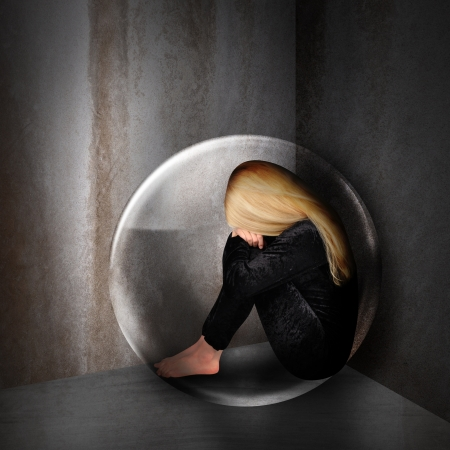 A young woman is depressed and sad in a bubble in a dark room  The girl has her head down and curled up in a corner   photo